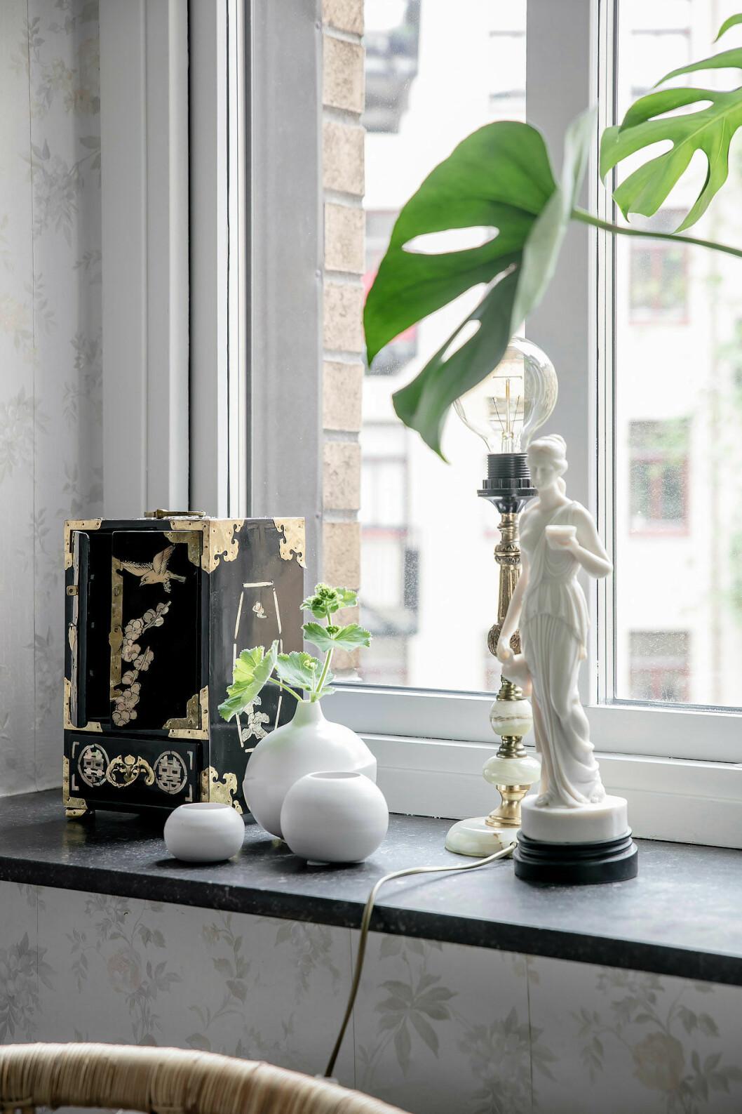 Fönsterbräda där personliga detaljer står bredvid en lampa och en växt
