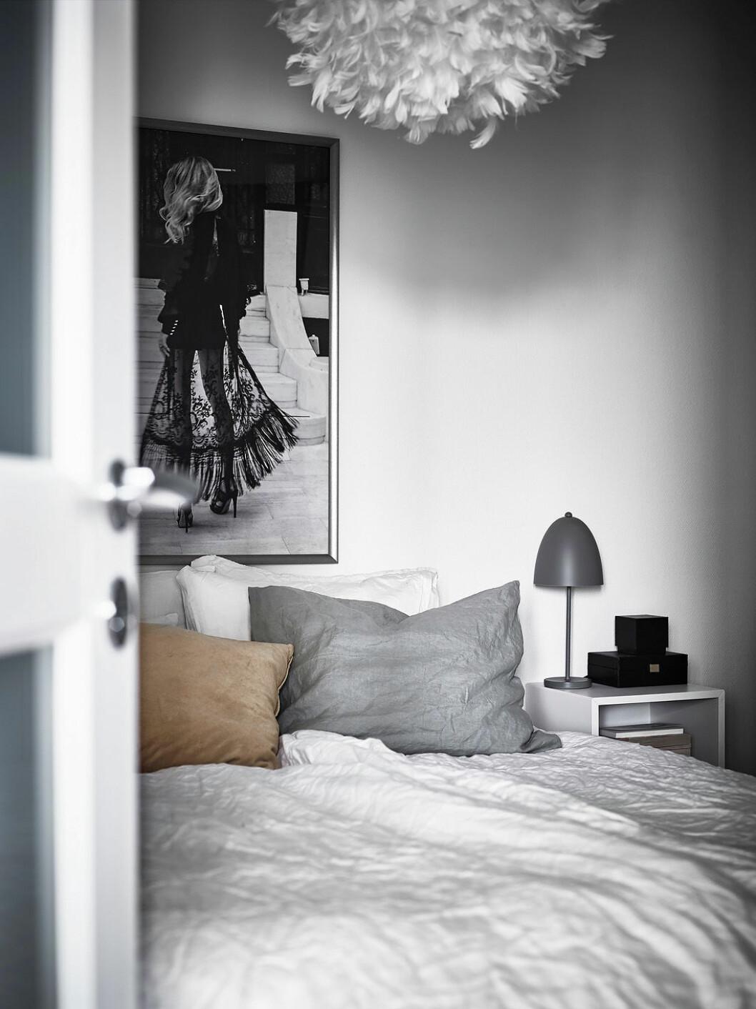 Vitmålat sovrum med fjäderlampa och kuddar i jordnära toner