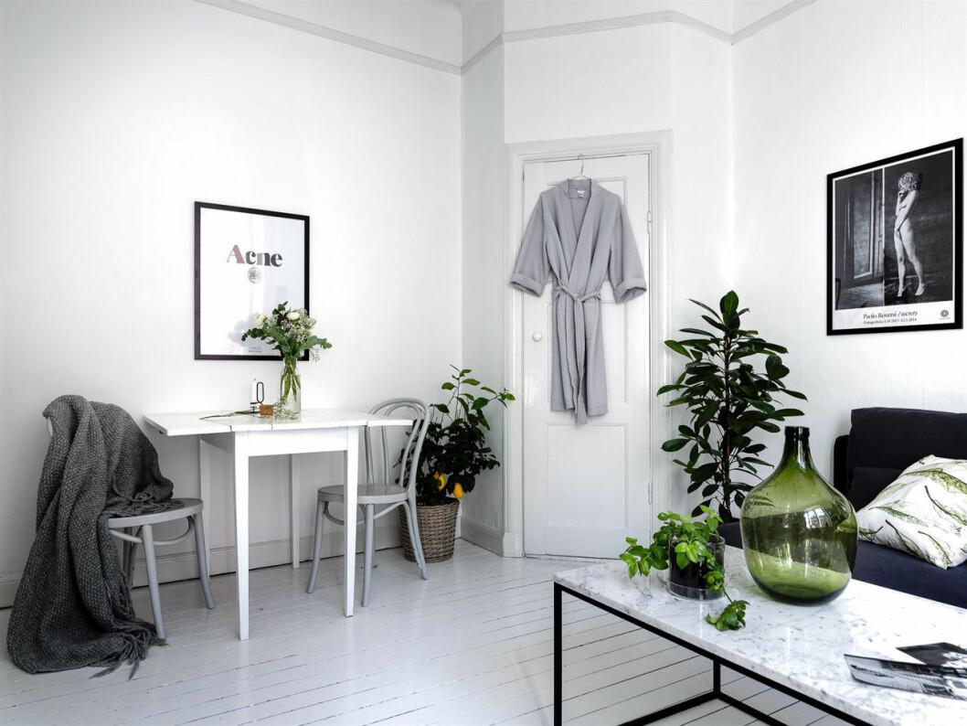Vitmålat vardagsrum med tavlor och marmorbord