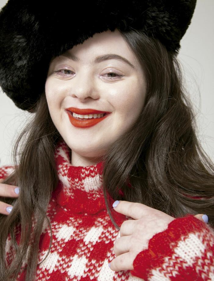 Ellie Goldstein i svart hatt och röda läppar