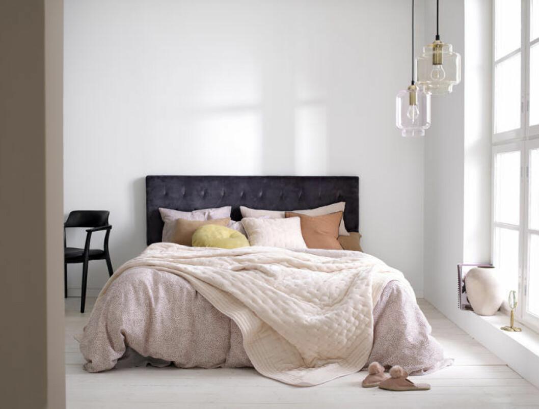 Sovrum med rosa bäddning och stoppad sänggavel i mörklila nyans. Våren 2018 på Ellos Home.