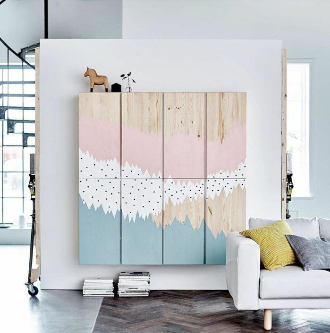 Fyra Ivarskåp upphängda på väggen och målade som en tavla i rosa och blått med ett vitt prickigt mönster