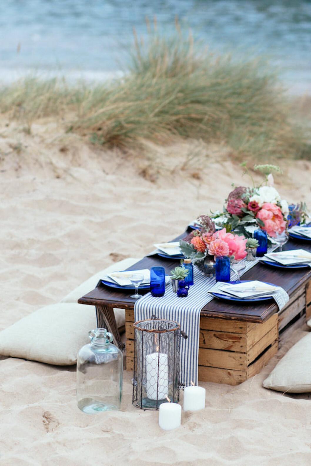 enkel dukning på stranden av äppellådor och sittdynor