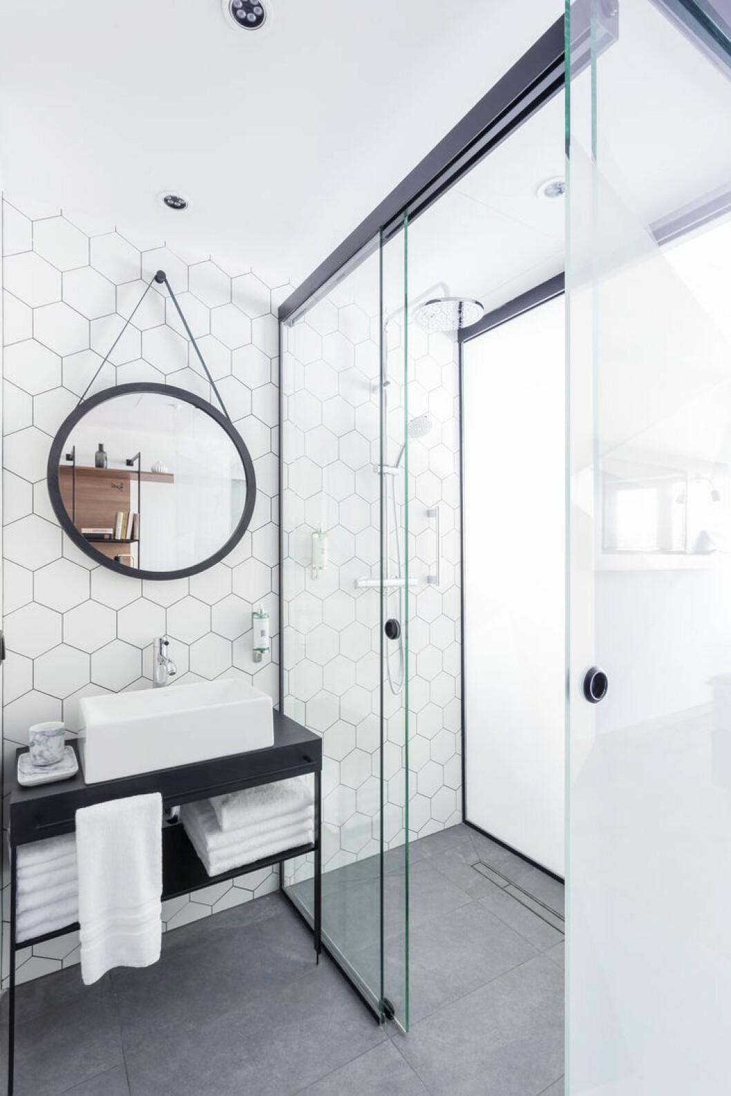 Stilrent badrum med gråa klinkerplattor och hexagonmönstrade, vita plattor på väggarna.