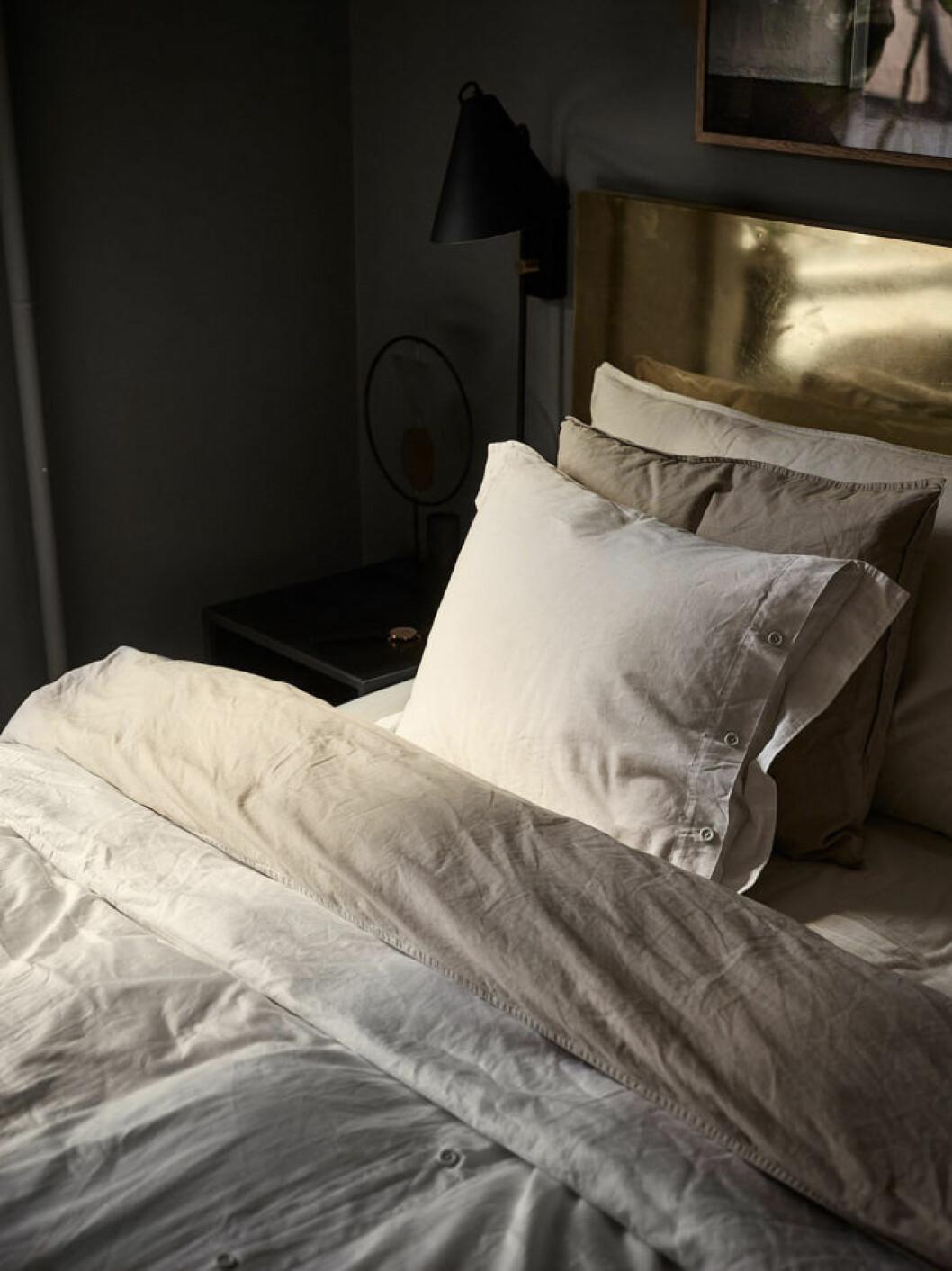 Sängkläder i naturfärg och sänggavel i mässing.