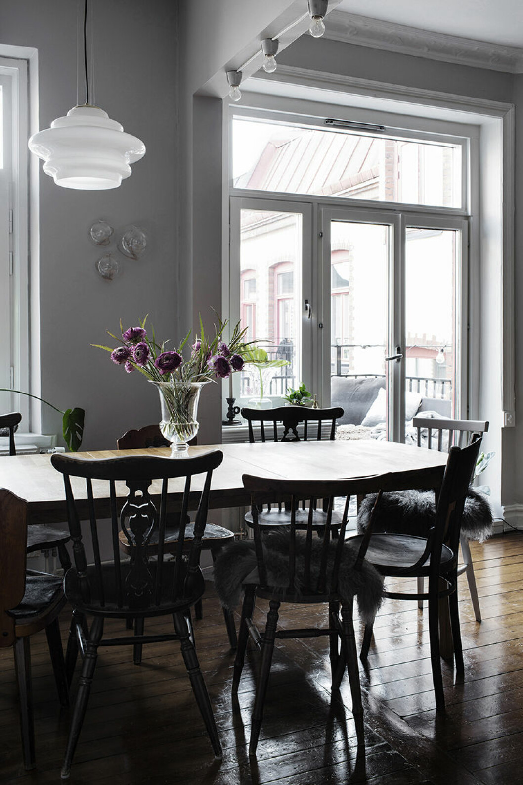 Matplats med rustika stolar runt och en bukett på bordet