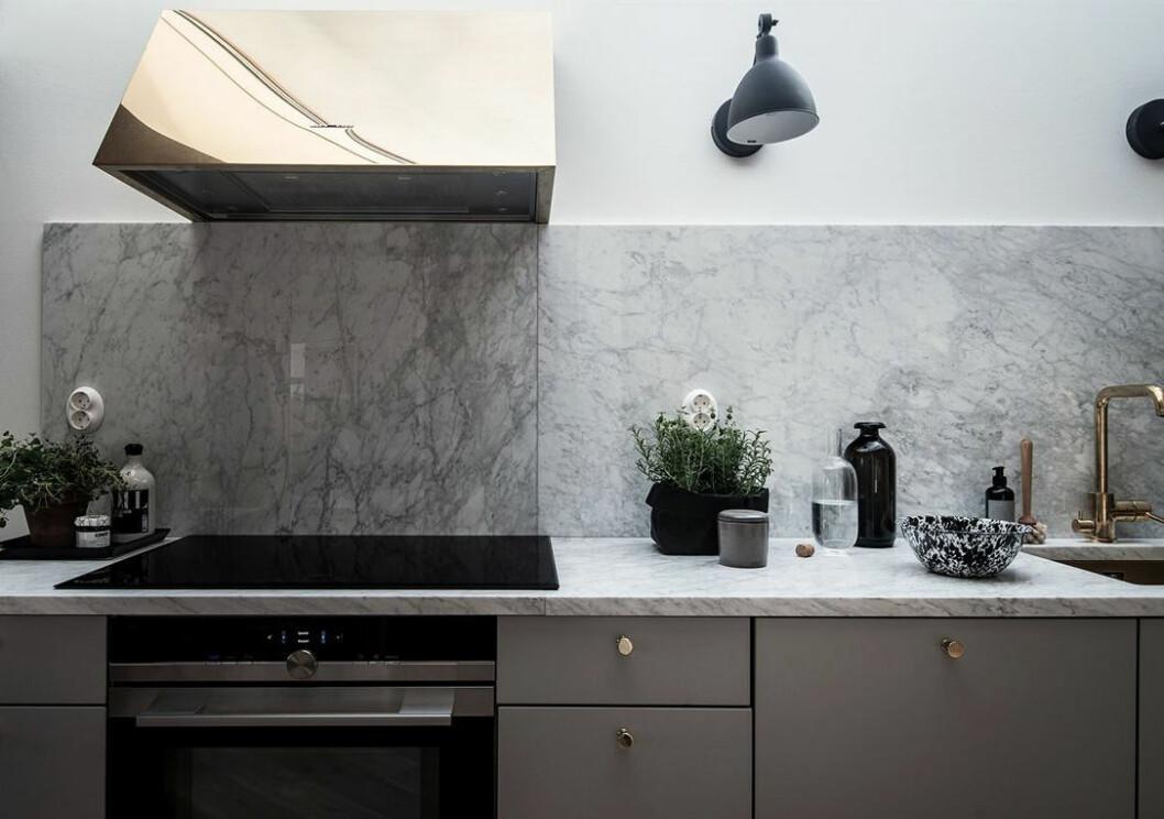Kök med mässingsfläkt och marmorskiva