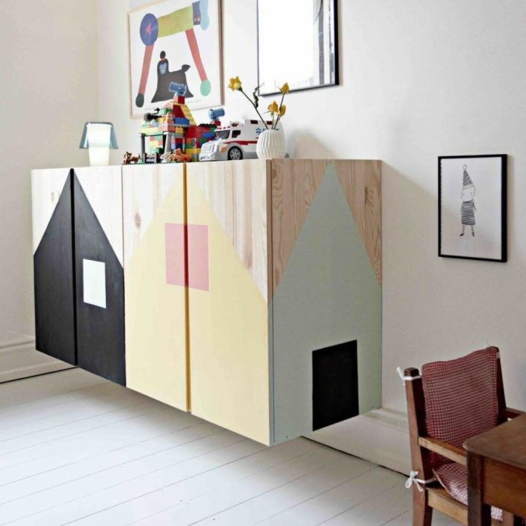 Två vägghängda Ivarskåp i ett barnrum som är mönstermålade som hus