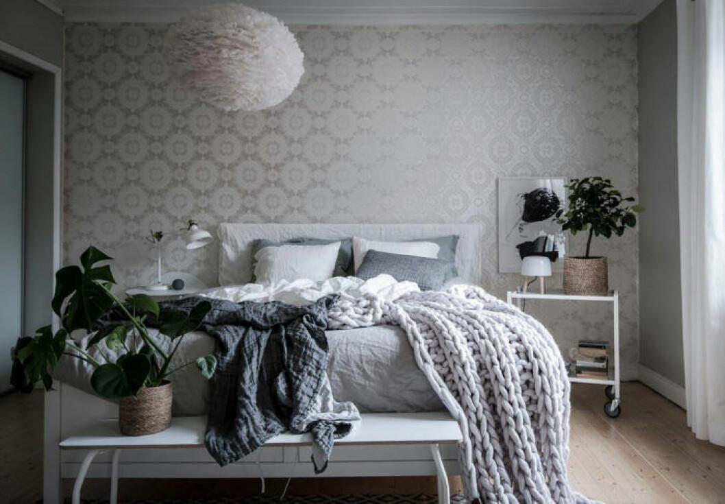 Mysigt sovrum med grovstickad filt, monstera och rund taklampa med fjädrar från Vita.