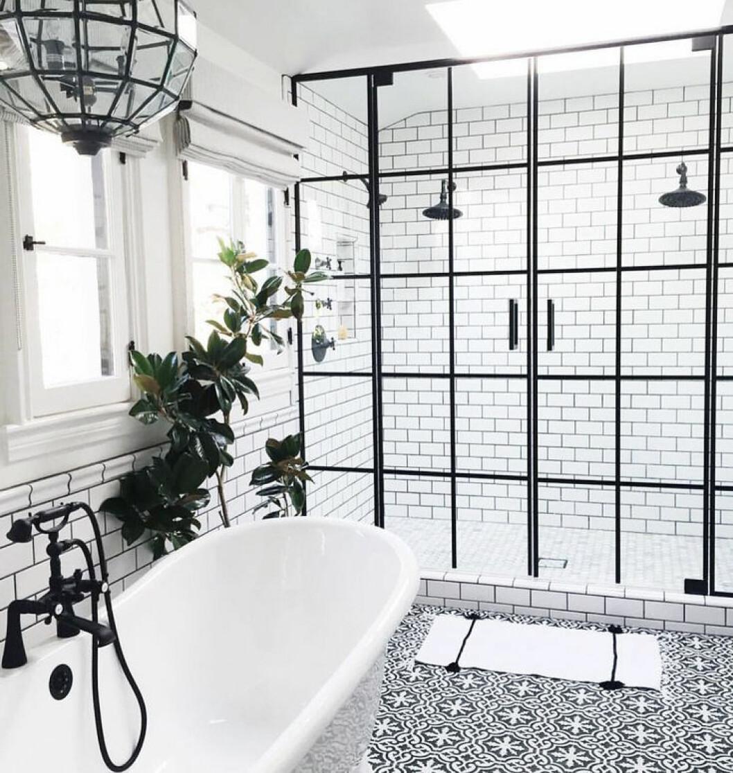 Svart/vitt mönstrade klinkerplattor på golvet, vita på väggen med svart fog.