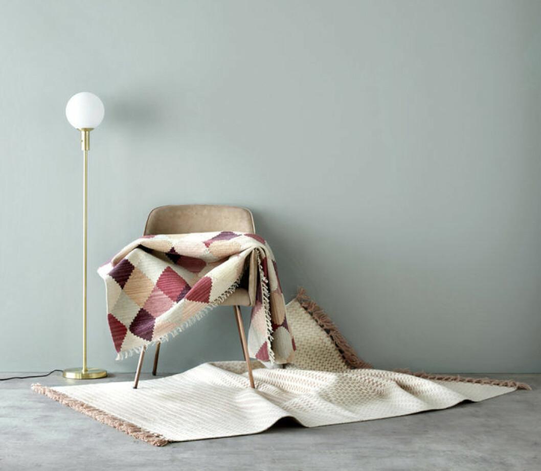 Lampa med guldfot och stol med mattor. Våren 2018 på Ellos Home.