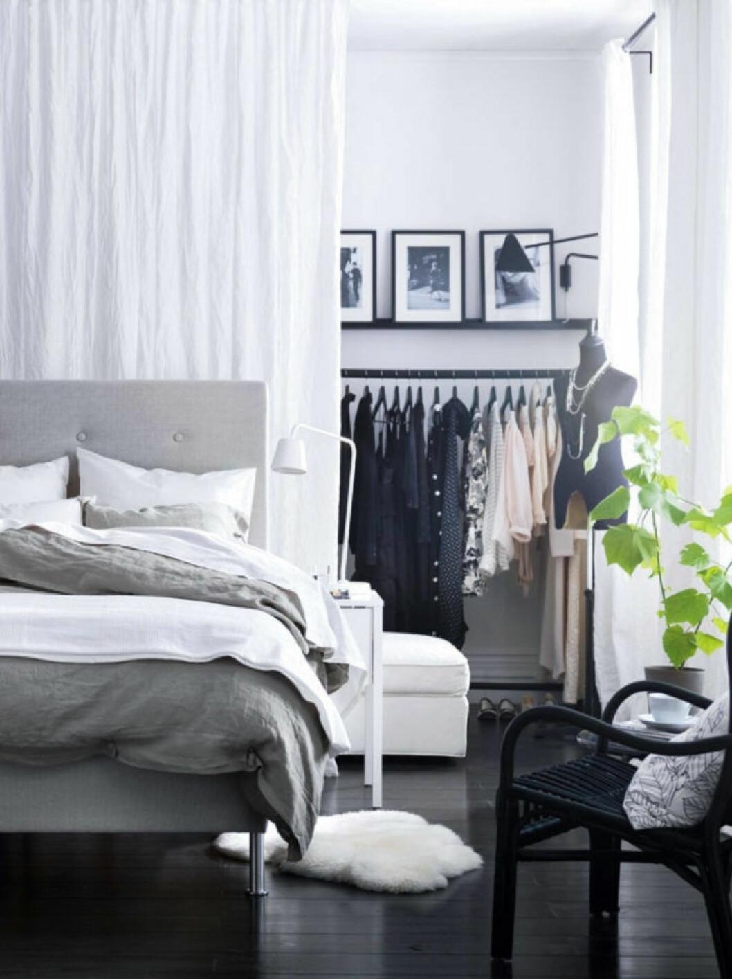 Sovrum med säng utskjuten från väggen och en liten walk-in-closet finns bakom en skir gardin