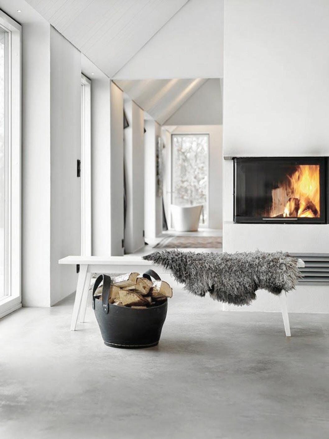 Braskamin i ett stilrent vardagsrum i vitt