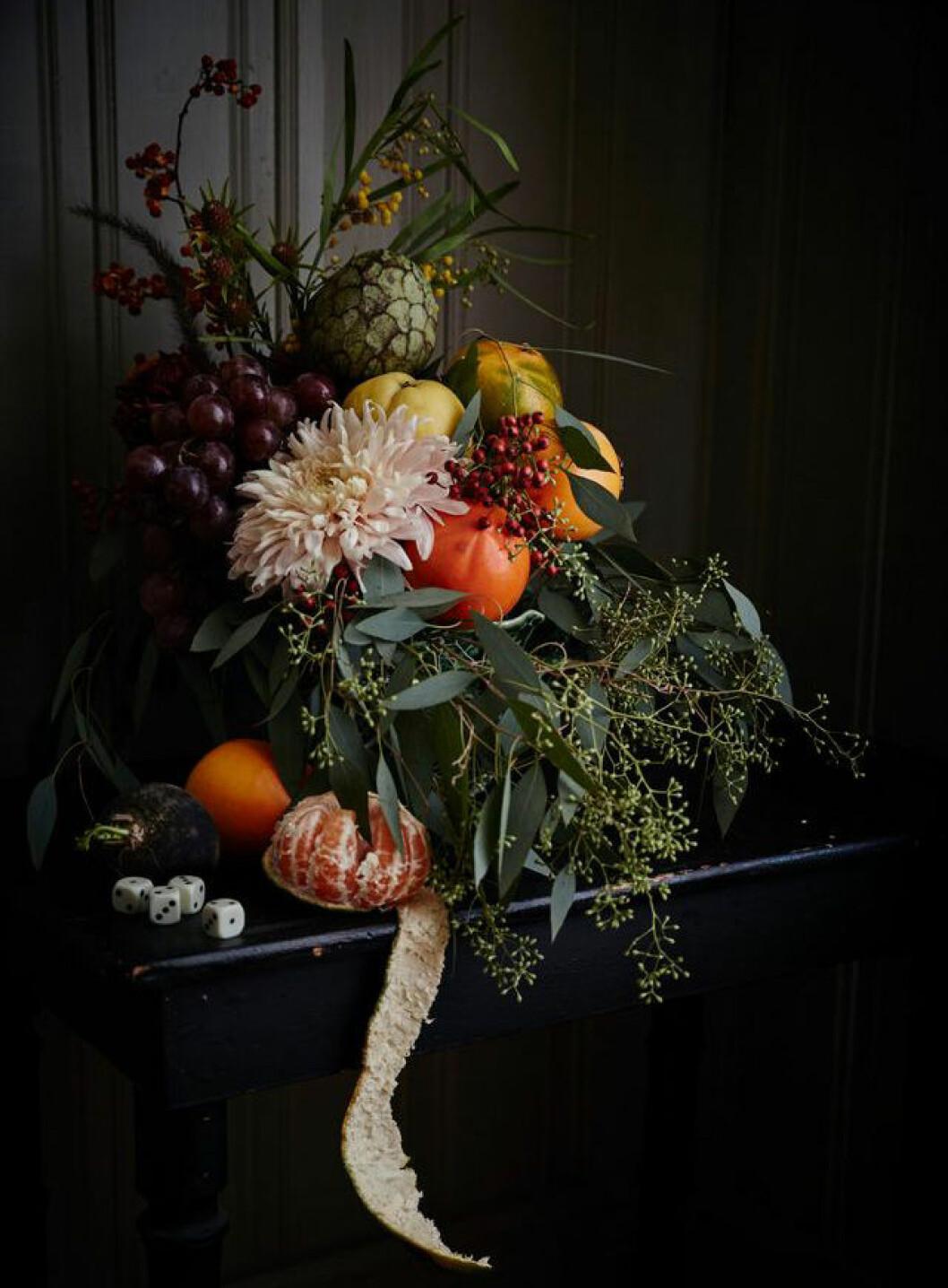 Dekorativ bukett med blandning av blommor, bär och frukt.