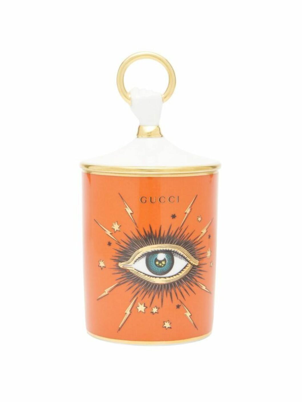 Lyxigt doftljus med en ikonisk ögonsymbol och vackert uttryck i orange från Gucci.