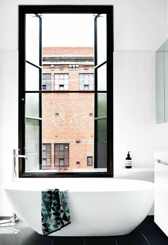 Fönster med svart fönsterkarm i ett i övrigt vitt badrum