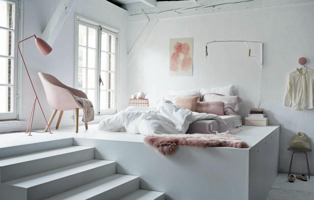 Säng placerat på ett litet podium som skapat snygga nivåskillnader i rummet