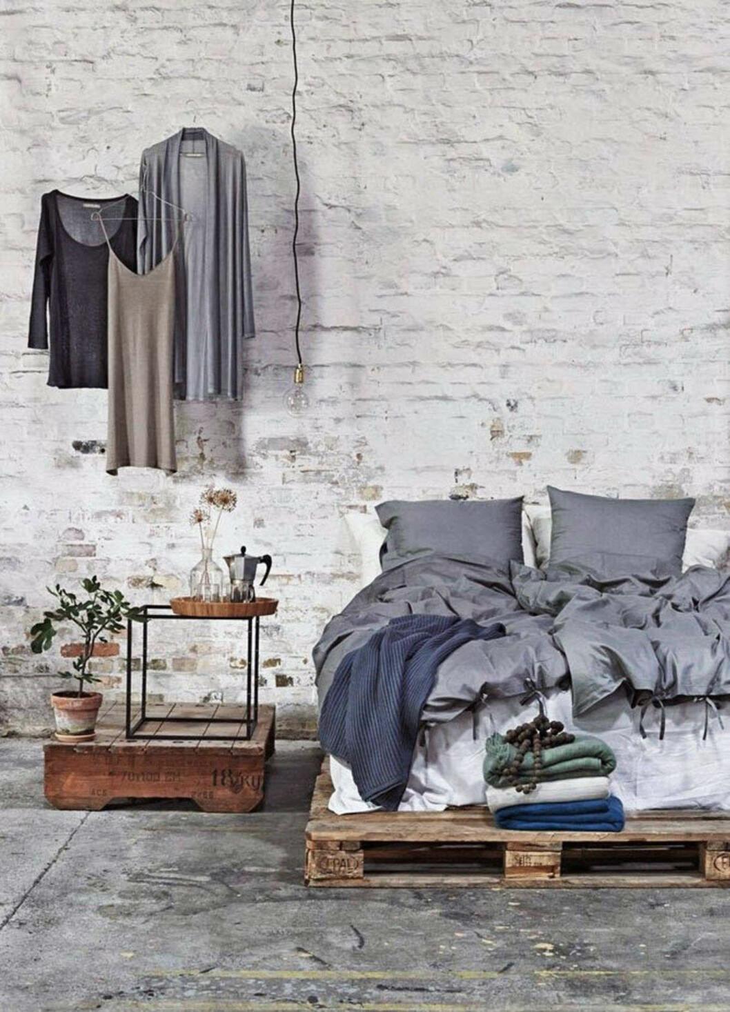 Vit tegelvägg och säng placerad på lastpallar för enhetlig rustik känsla