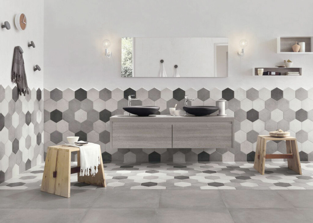 Hexagonformat kakel i olika nyanser av grått i ett badrum.