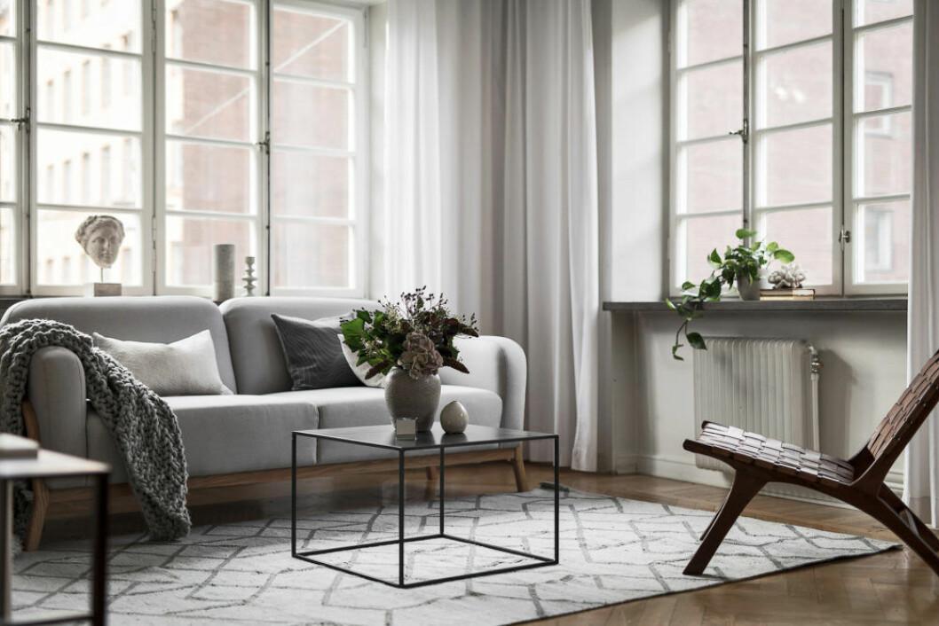Stora generösa fönster med sparsmakade inredningsdetaljer, gardiner i hörnet fyller tomrum