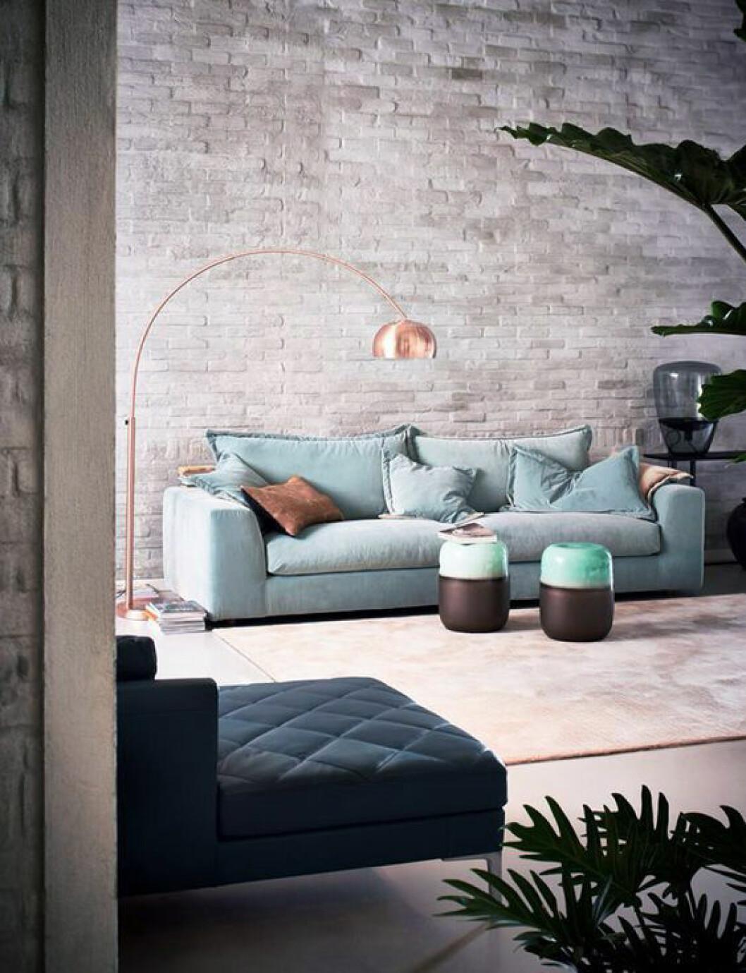 Tegelvägg mjukas upp av pastellblå soffa och mjuk sammet