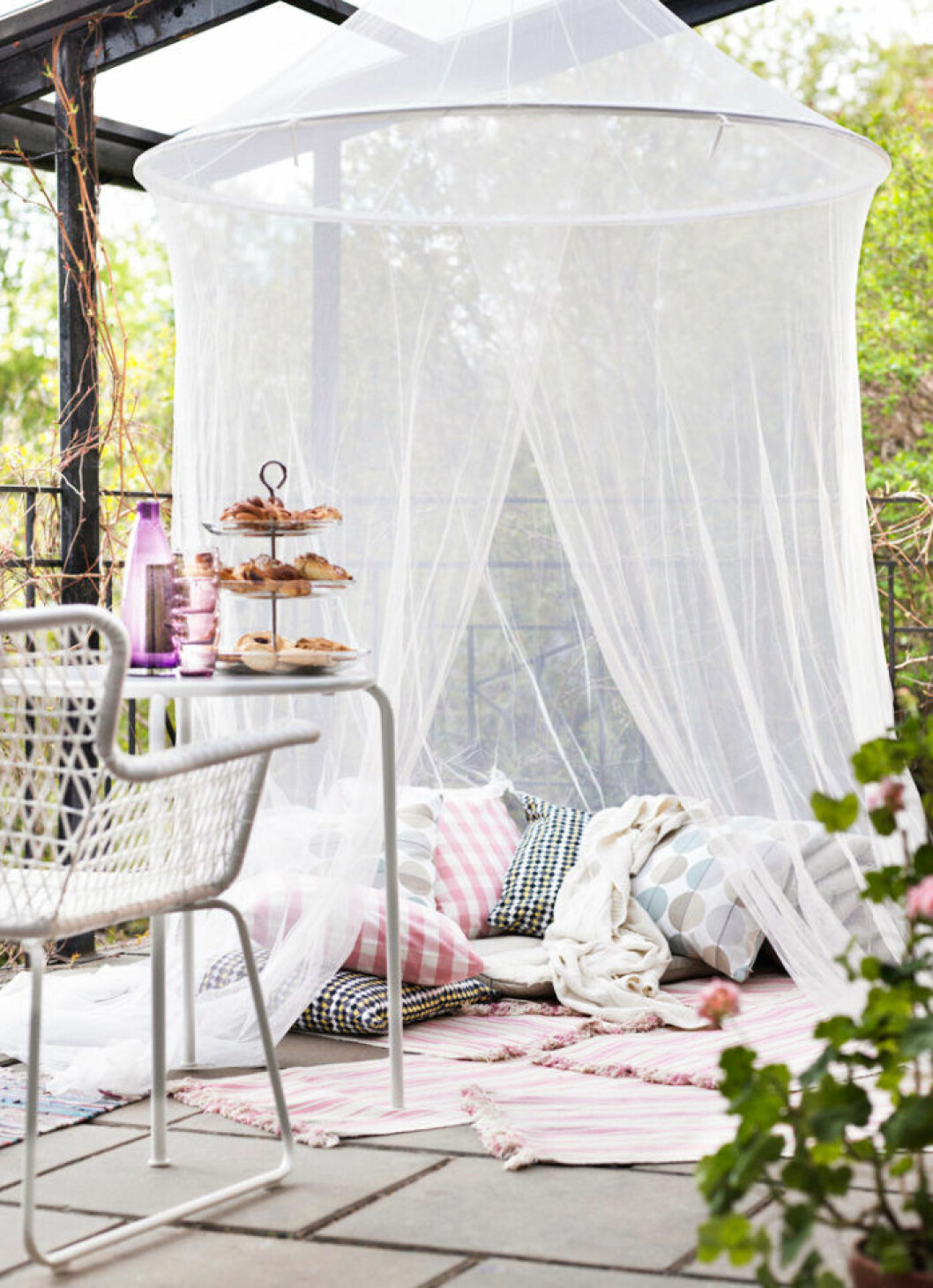 Scandinavian balcony decorated with tulle and pillows.