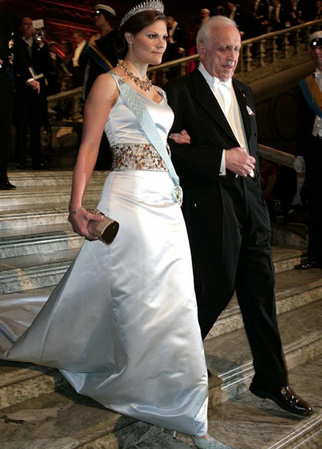 Kronprinsessan Victoria i en vit klänning med skärp.