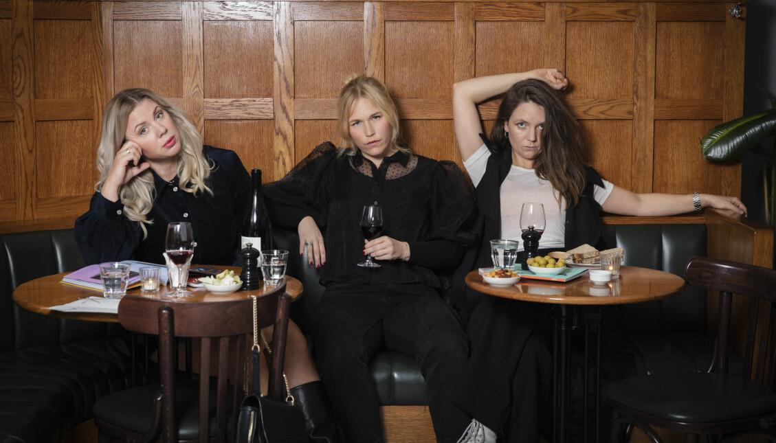 Tre kvinnor sitter ner och kollar in i kameran.