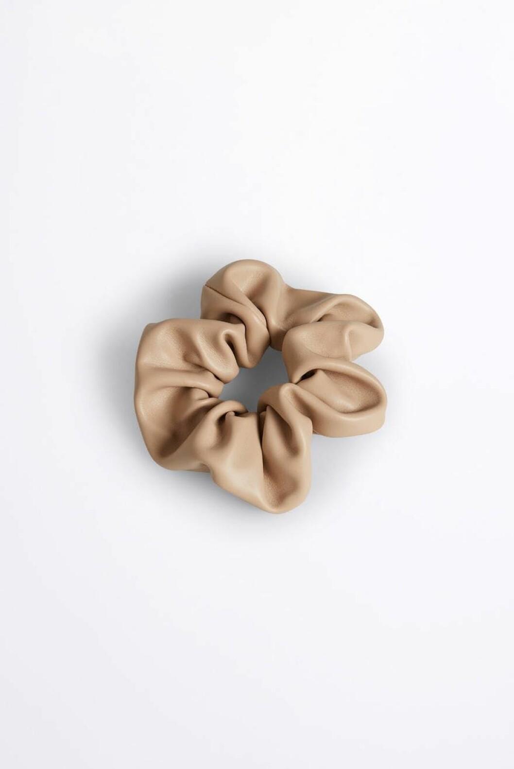 Piffa hårsvansen med en snygg snodd som denna i beige skinnimitation från Gina tricot.