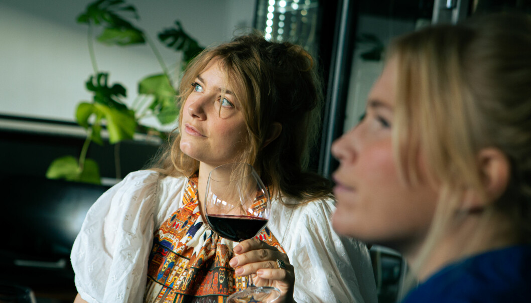 Två kvinnor tittar ut och ler. En håller i ett vinglas.