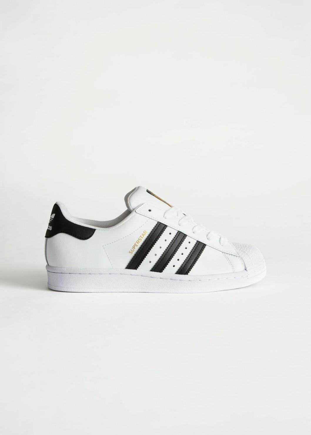 Vita sneakers med detaljer i svart från Adidas.