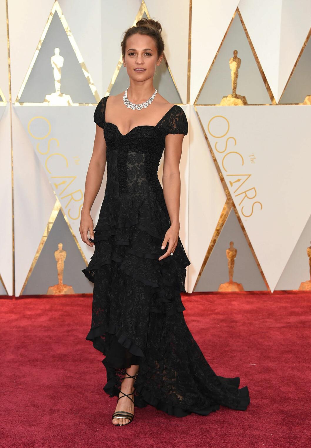 Alicia Vikander i svart klänning och vackert halsband