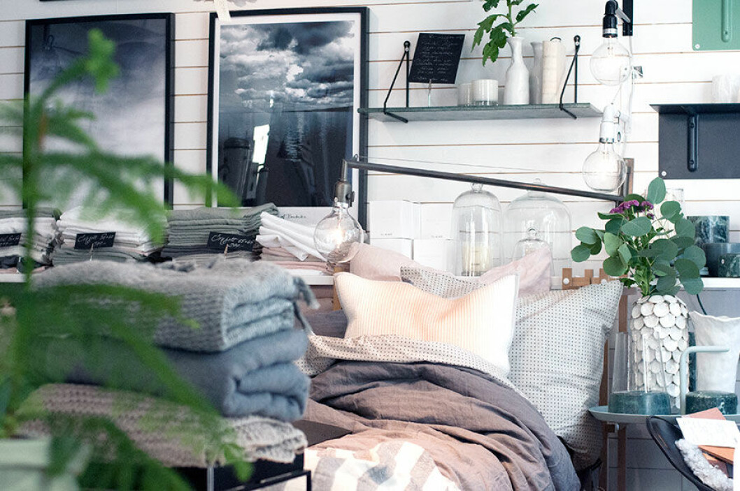 En vackert bäddad säng och tavlor i Alvhembutiken.