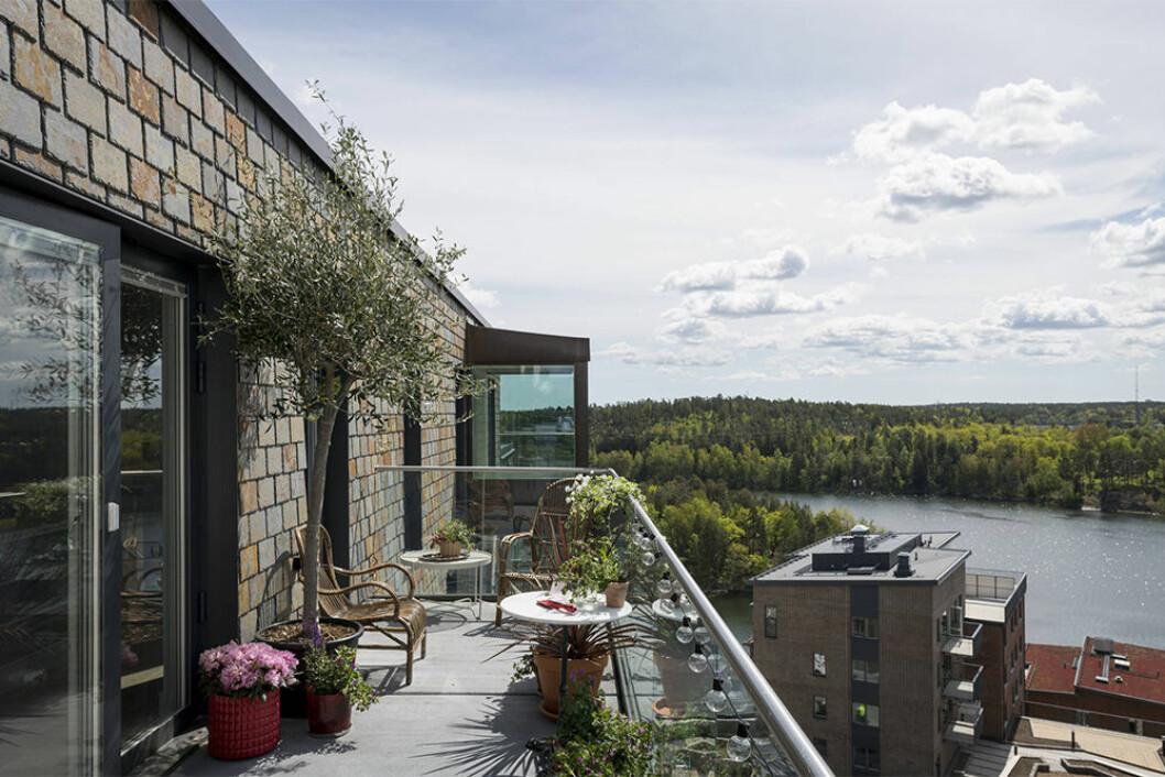 Stor balkong med grönska och sjöutsikt