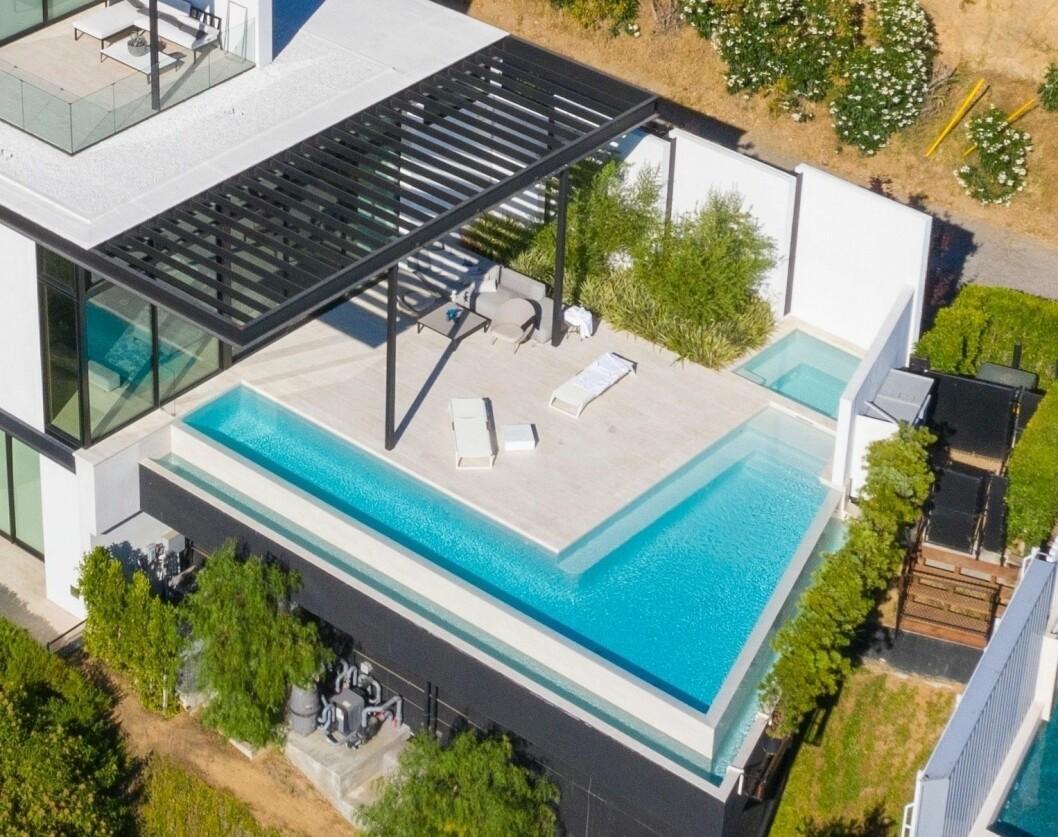En fyrkantig pool utanför ett hus