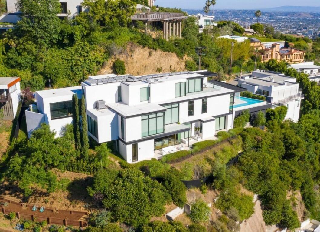 vitt hus med glas som ligger på en kulle med massa grönt omkring