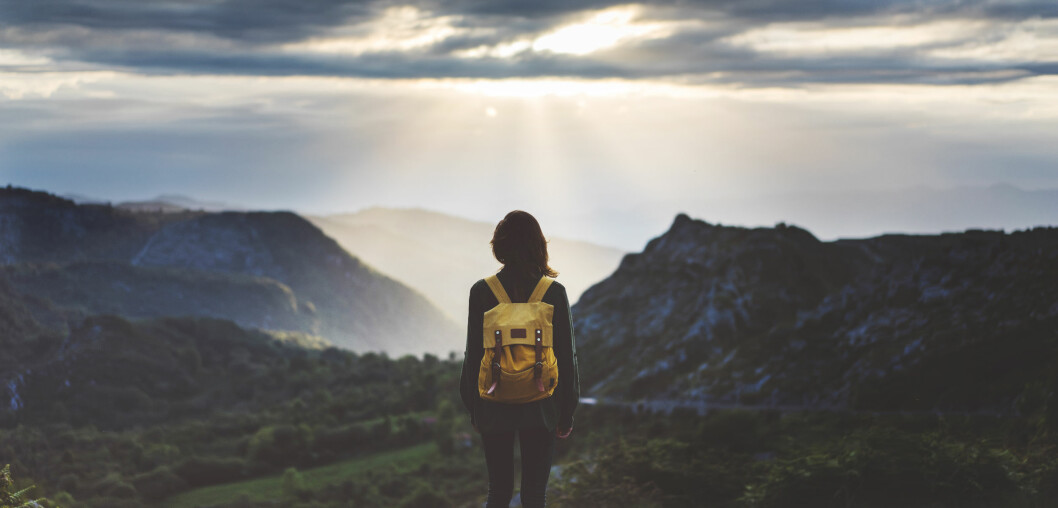 Kvinna med ryggsäck tittar ut över berg och hav