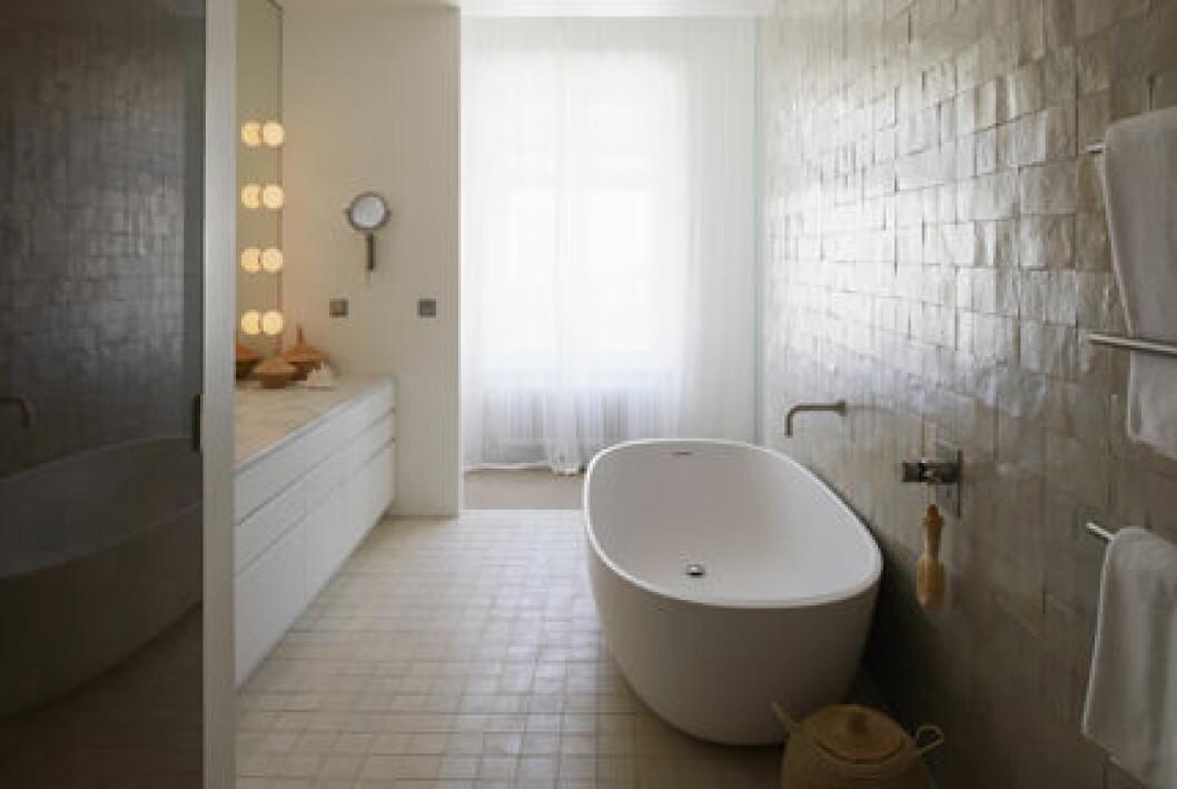 Badrum med badkar och buckligt kakel.