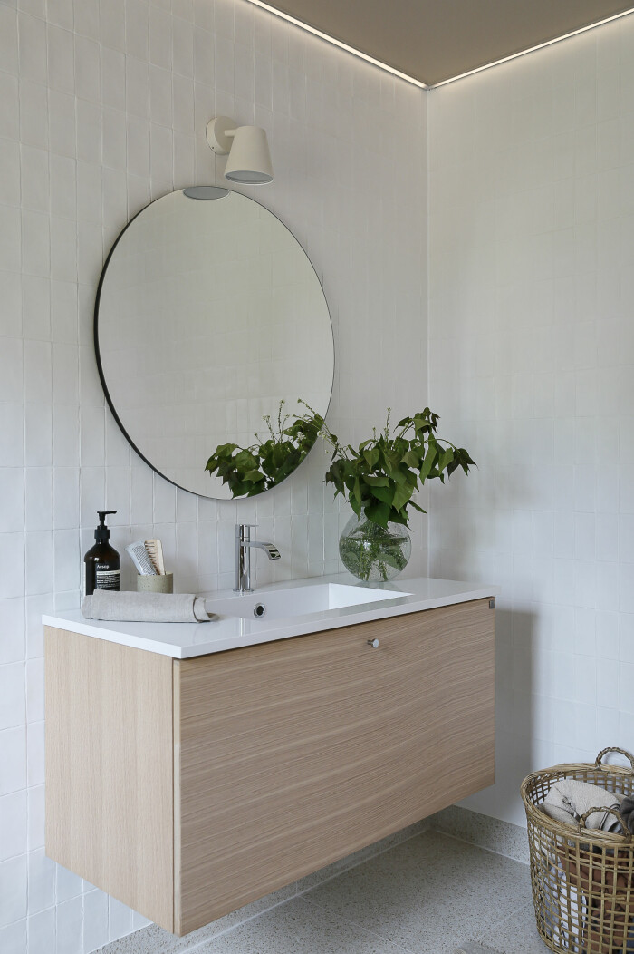 badrum med kommod i ljust trä och vita kaklade väggar från ballingslöv