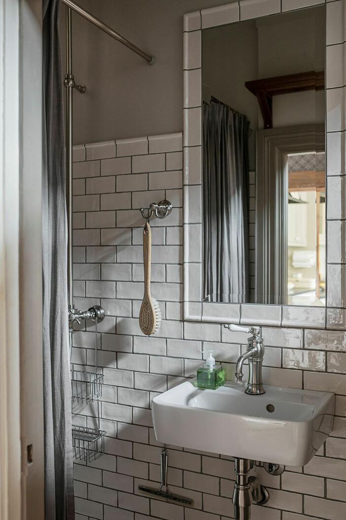 badrum med vitt kakel och kaklad spegel