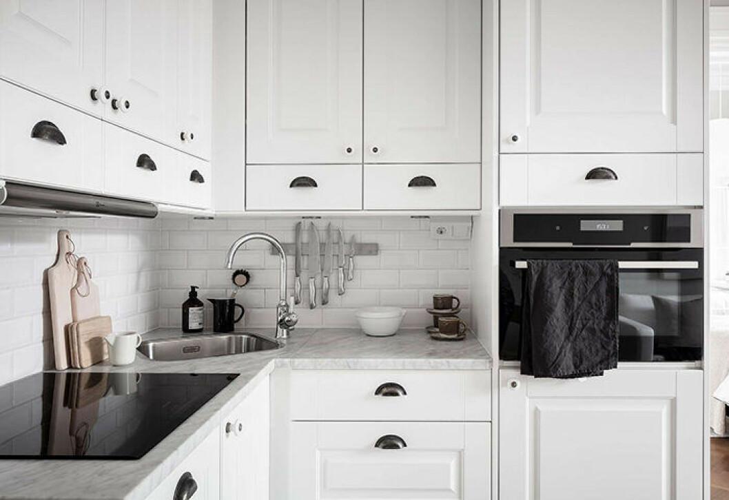 Vitt klassiskt kök med bänkskiva i marmor