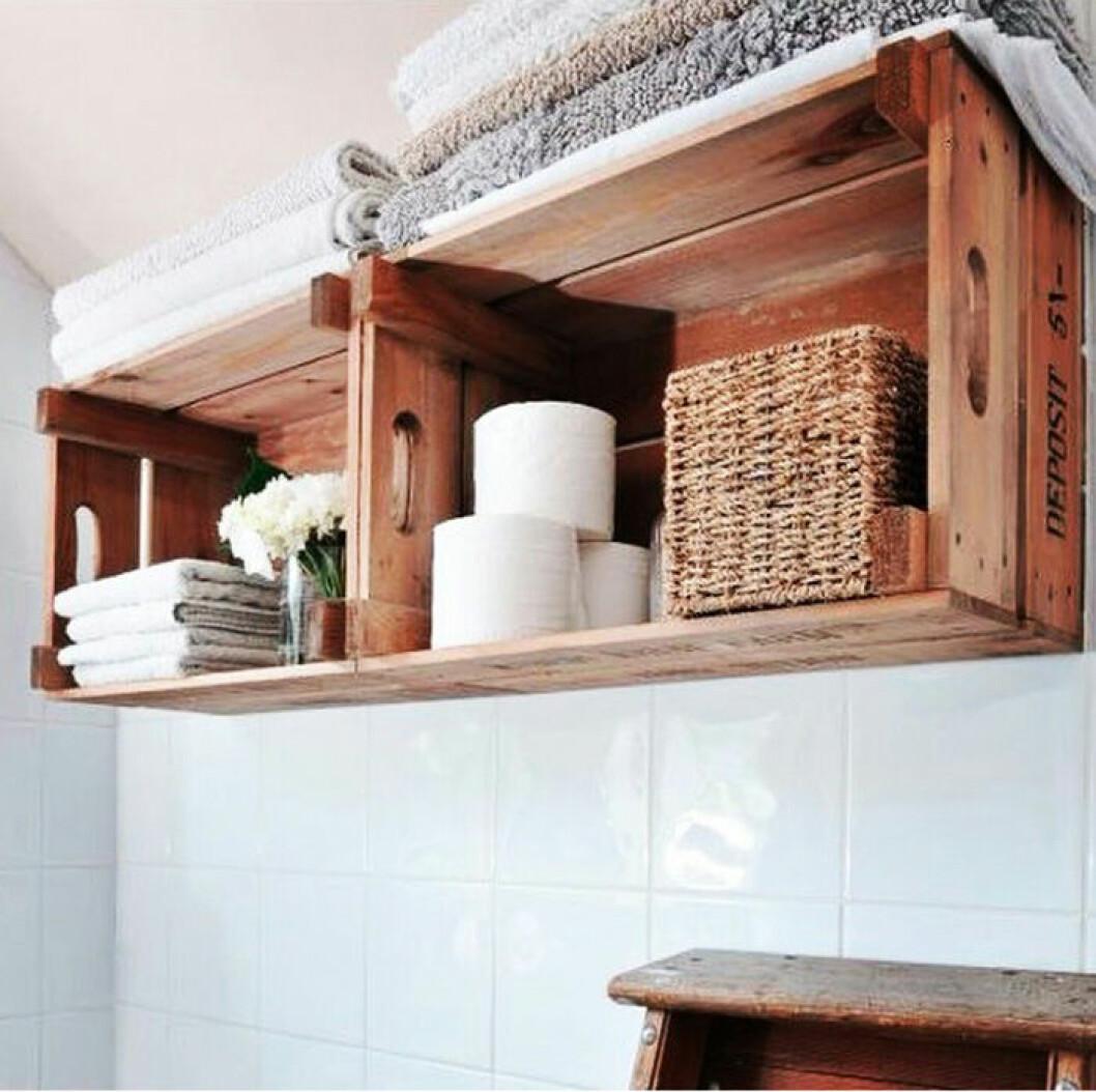 Gamla äppellådor uppskruvade på väggen och är förvaring för handdukar och toalettpapper