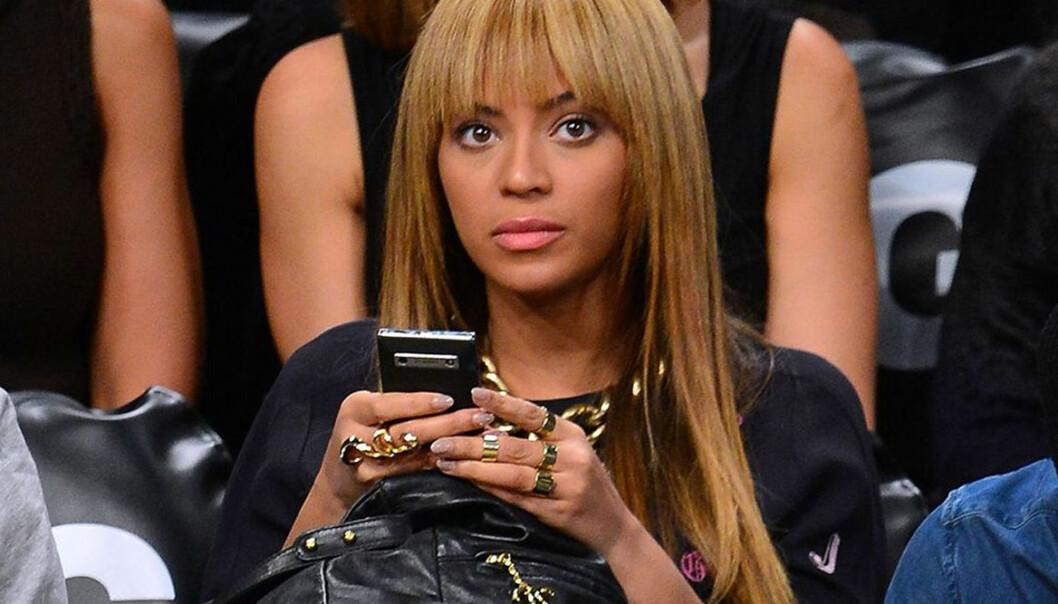 Beyonce sitter med sin telefon