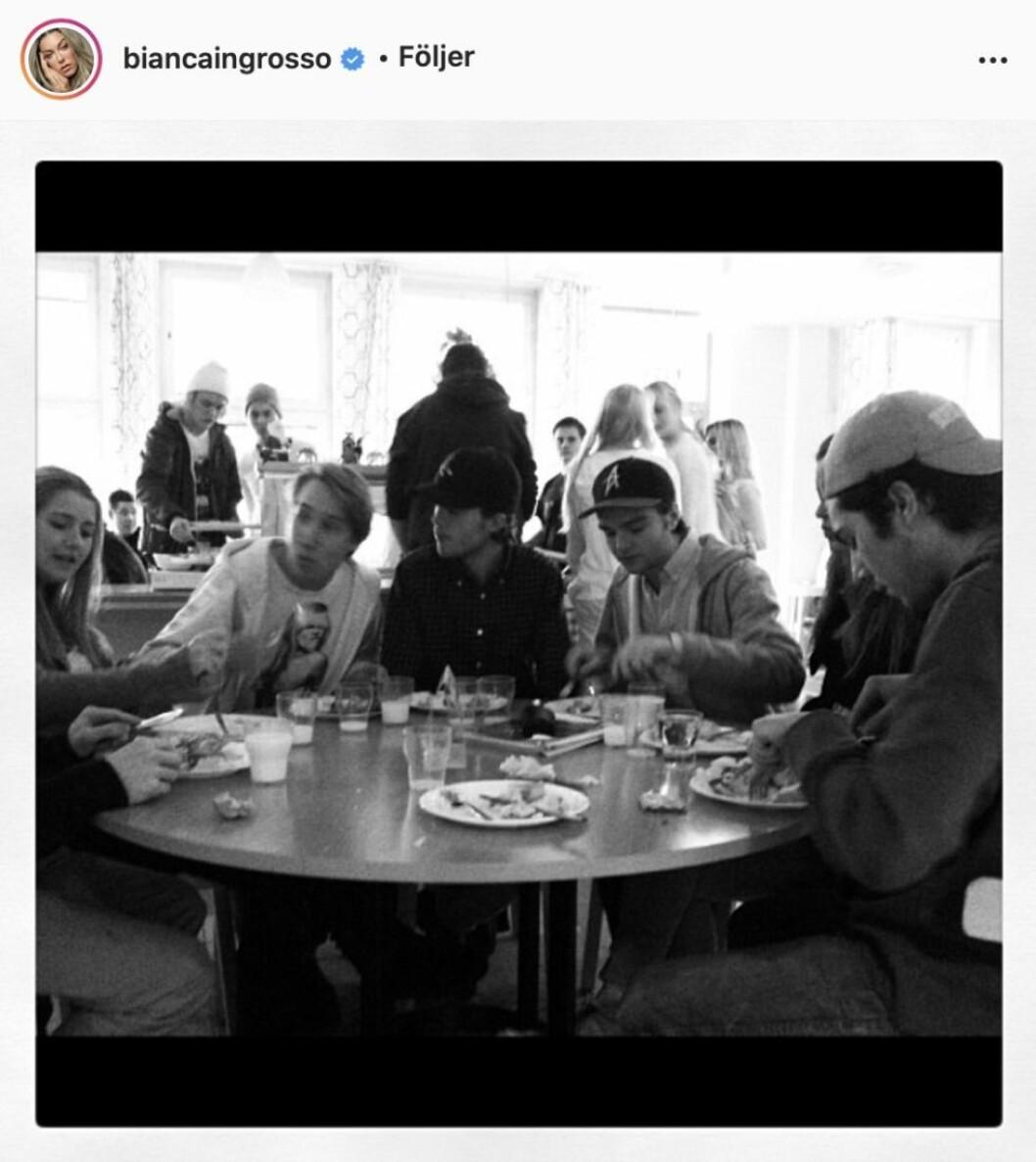 En svartvitbild med ungdomar som sitter runt ett bord och äter