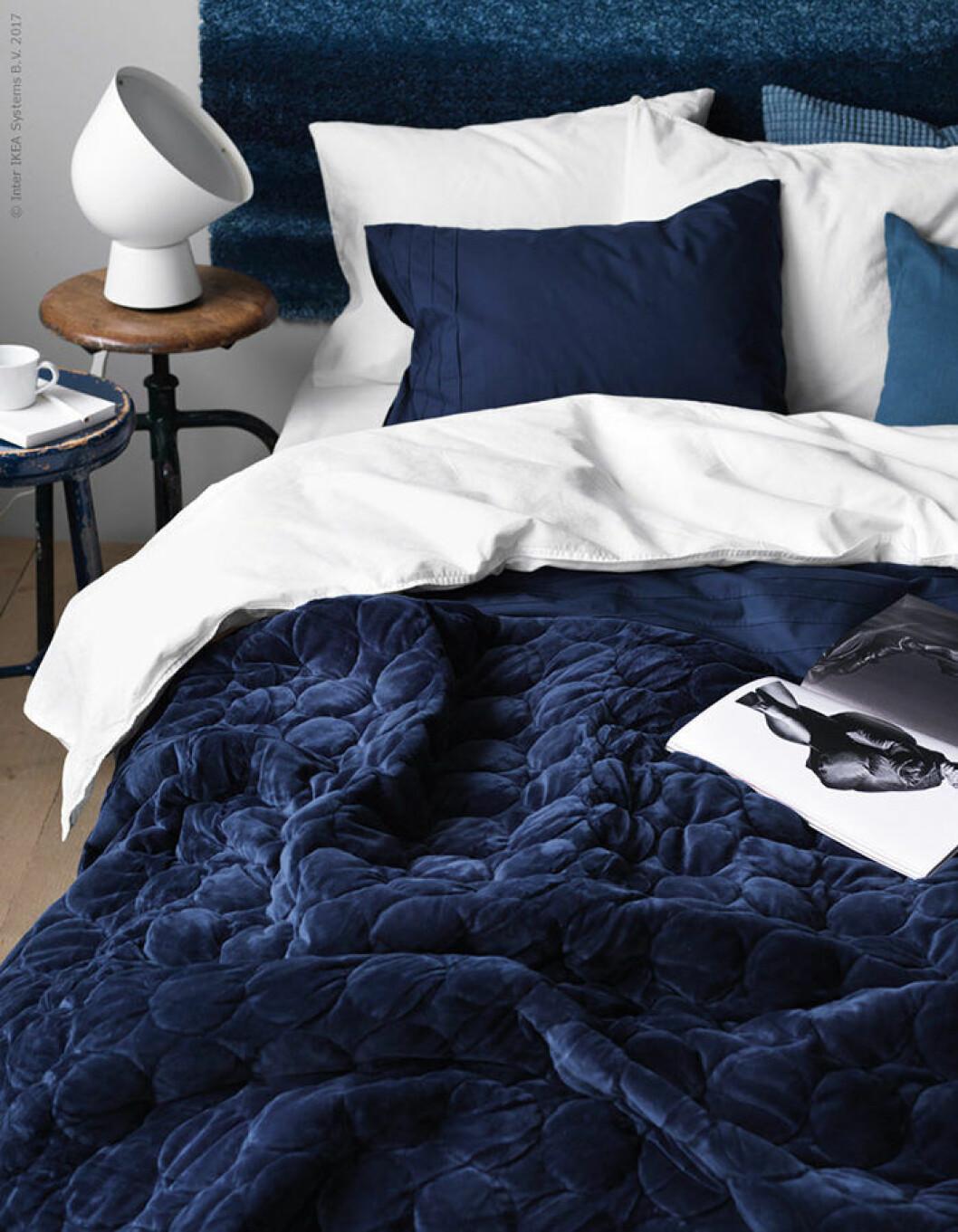 Säng med blått överkast, blåa kuddar och blå sänggavel