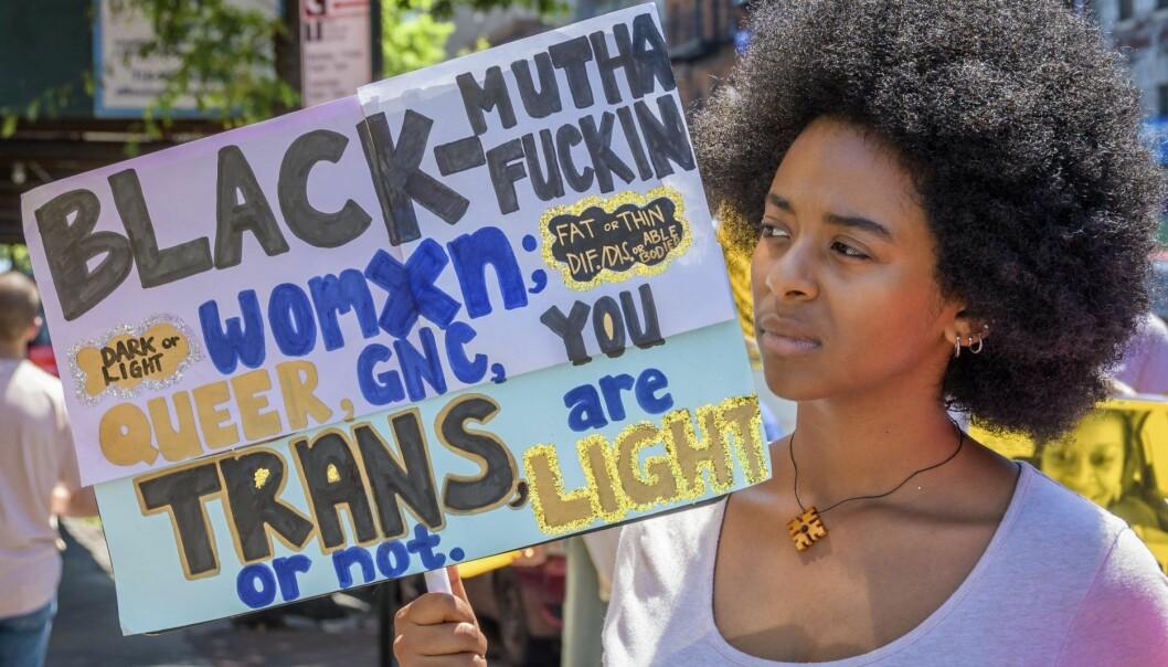 en kvinna håller upp en protestskylt