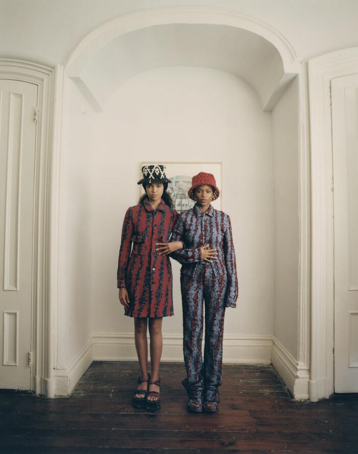 Aun'Jel bär en kappa och skor, Na'Jeen har på sig kavaj, topp, byxor och skor, allt från Bottega Veneta