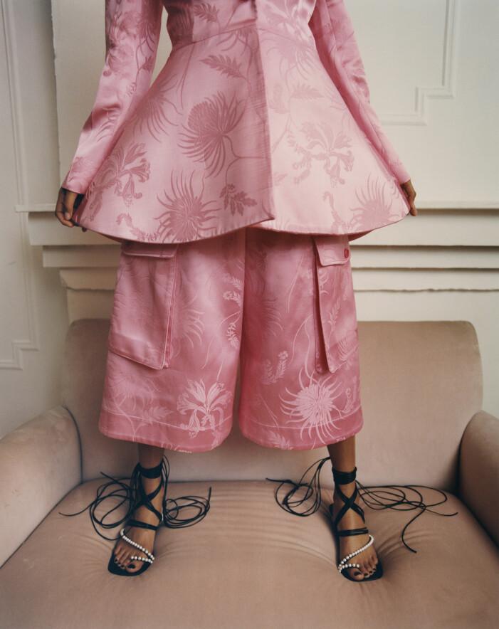 Modellen har på sig kavaj, shorts och sandaletter från JW Anderson