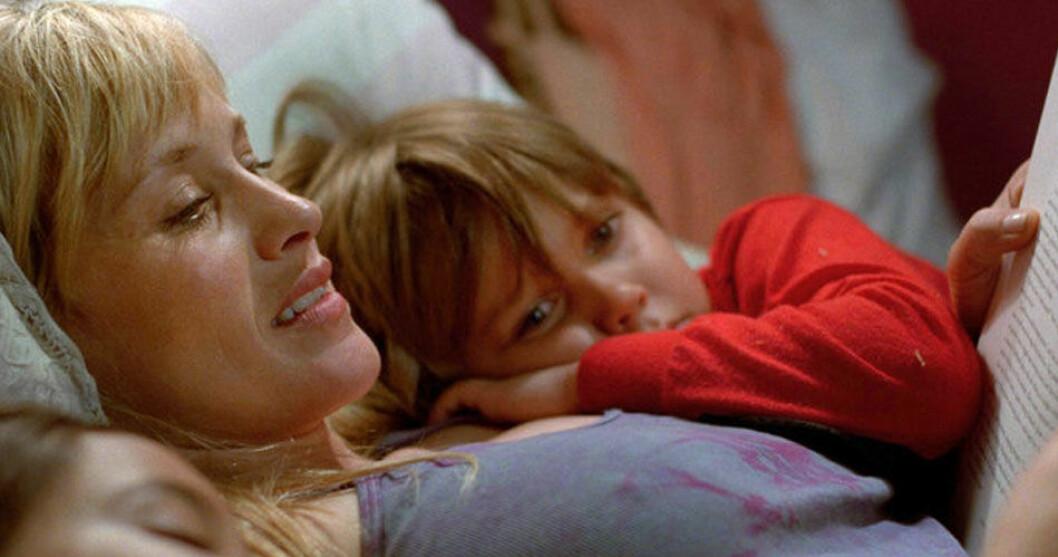 mamma läser saga för sina barn i sängen