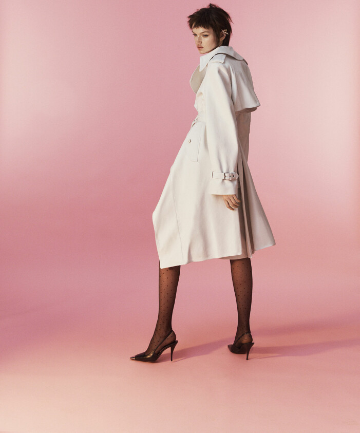 Modellen bär en vit trenchcoat från Alexander McQueen